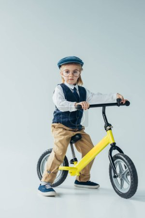 Photo for Kid in retro vest and cap riding bike and looking at camera on grey background - Royalty Free Image