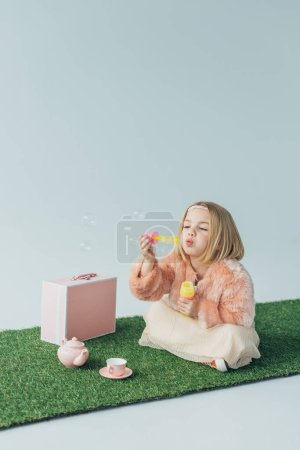 Photo for Cute kid with crossed legs sitting on grass rug and blowing soap bubbles isolated on grey - Royalty Free Image