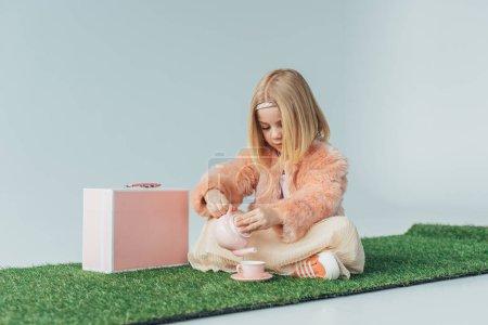 Foto de Niño sentado con las piernas cruzadas jugando con juguete rosa platos aislados en gris - Imagen libre de derechos