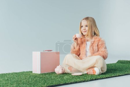 Photo for Smiling child sitting with crossed legs playing with pink toy dishes isolated on grey - Royalty Free Image