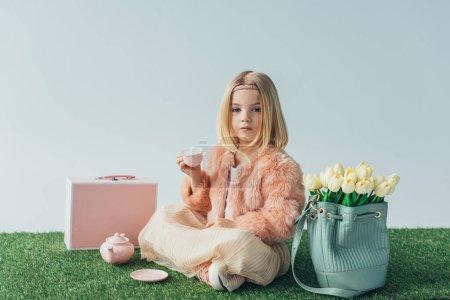 Foto de Niño con las piernas cruzadas jugando con platos de juguete y mirando a cámara aislada en gris - Imagen libre de derechos