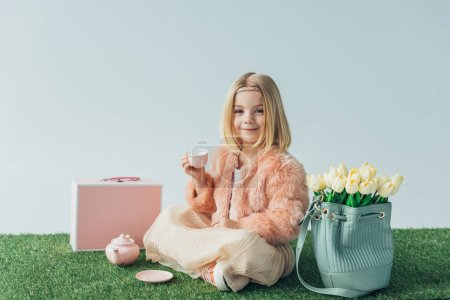 Photo for Smiling child with crossed legs playing with toy dishes and looking at camera isolated on grey - Royalty Free Image