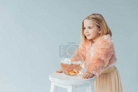 Photo pour Cute kid en manteau de fourrure et jupe avec aquarium à la recherche de suite isolé sur fond gris - image libre de droit