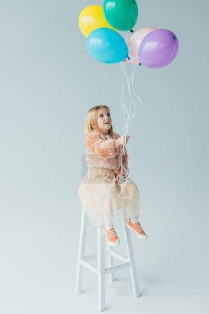 Photo pour Cute kid en manteau de fourrure et jupe assis sur la chaise haute et tenant des ballons - image libre de droit