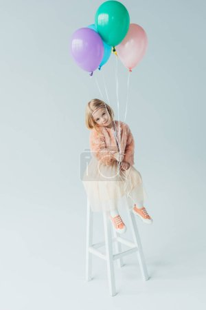Photo for Cute kid in faux fur coat and skirt sitting on highchair, looking at camera and holding balloons - Royalty Free Image