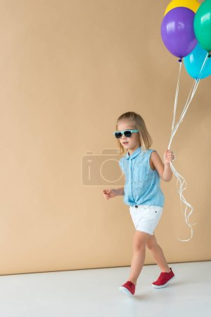 Photo for Cute kid in sunglasses, shirt and shorts walking and holding balloons - Royalty Free Image