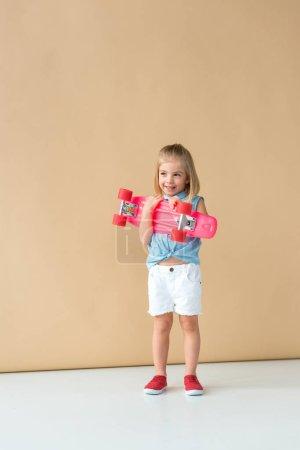 Foto de Sonriente y lindo chico en camisa y pantalones cortos con junta de penny rosa sobre fondo beige - Imagen libre de derechos