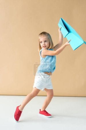 Photo for Adorable and smiling kid in shirt and shorts playing with paper plane - Royalty Free Image