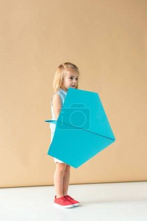 Foto de Adorable niño jugando con avión de papel azul sobre fondo beige - Imagen libre de derechos