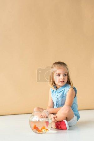 Photo pour Cher enfant assis sur le sol avec Fishbowl et regardant loin sur fond beige - image libre de droit