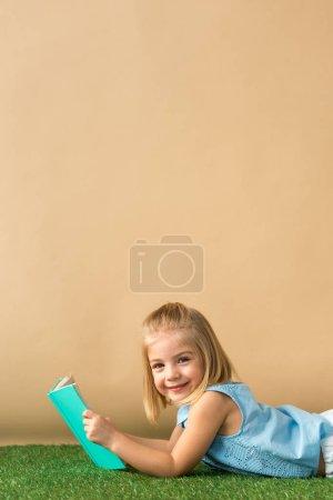Foto de Sonriente y lindo chico acostado en la alfombra de hierba y sosteniendo libro sobre fondo beige - Imagen libre de derechos