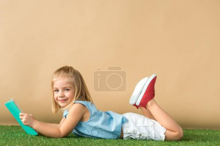 Photo for Smiling and cute child lying on grass rug and holding book on beige background - Royalty Free Image