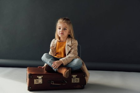 Photo for Pensive child sitting with crossed legs on leather suitcase on black background - Royalty Free Image