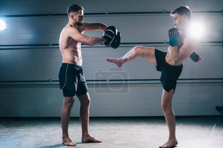 Photo for Strong muscular shirtless mma fighter practicing high kick with another sportsman - Royalty Free Image