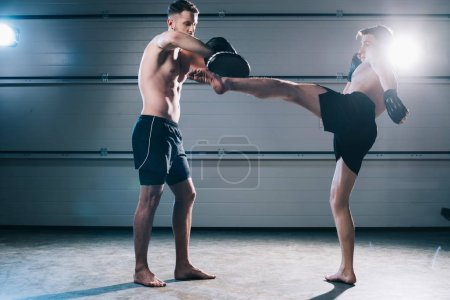 Photo for Strong muscular shirtless mma fighter practicing high kick with another sportsman during training - Royalty Free Image