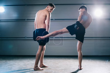 Photo for Back view of strong muscular barefoot mma fighter practicing low kick with another sportsman - Royalty Free Image