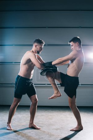Photo pour Athletic muscular barefoot mma fighter practicing kick with another sportsman during training - image libre de droit