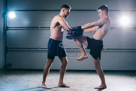 Photo pour Athletic muscular mma fighter practicing kick with another sportsman during training - image libre de droit