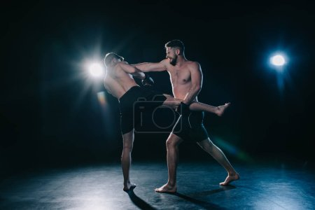 Photo for Shirtless mma fighter kicking another sportsman during muay thai training - Royalty Free Image