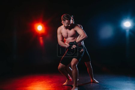 Photo for Strong mma fighter doing clinch to another sportsman behind back - Royalty Free Image