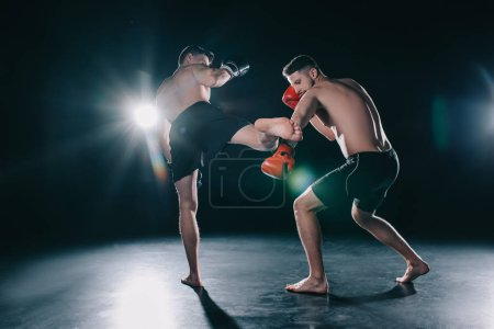 Photo for Strong mma fighter kicking another sportsman with leg in arm - Royalty Free Image