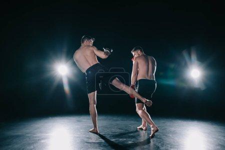 Photo pour Combattant de mma fort un autre sportif de coups de pied dans la jambe au cours de la formation - image libre de droit