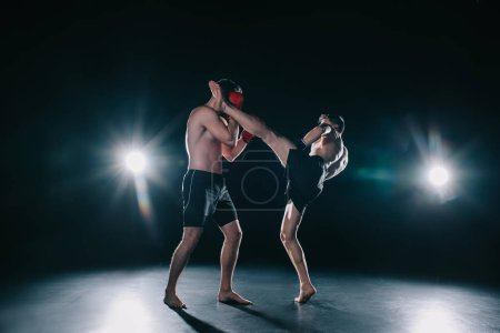 Photo for Strong mma fighter kicking another sportsman in head during fight - Royalty Free Image
