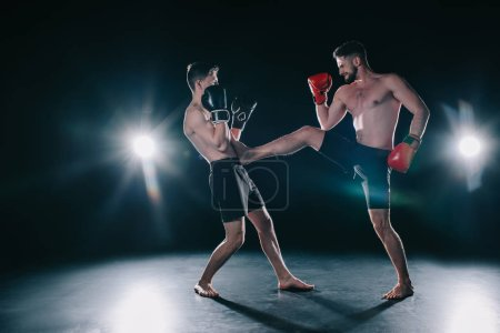 Photo for Shirtless muscular mma fighter in boxing gloves kicking another in torso - Royalty Free Image