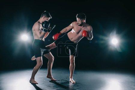 Photo pour Combattant de mma musclé torse nu dans les gants de boxe, un autre coup de pied dans la jambe - image libre de droit