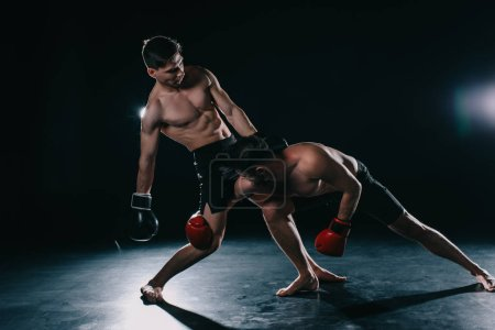 Photo for Shirtless strong muscular mma fighter in boxing gloves clinching another - Royalty Free Image