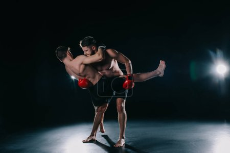 Photo for Strong muscular mma fighter in boxing gloves clinching another - Royalty Free Image