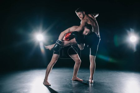 Photo for Barefoot strong muscular mma fighter in boxing gloves clinching another while sportsman kicking him - Royalty Free Image