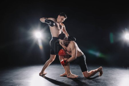 Photo for Barefoot strong muscular mma fighter in boxing gloves clinching another while sportsman punching him - Royalty Free Image