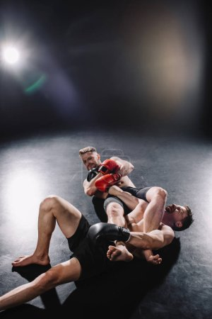 Photo pour Strong shirtless mma fighter doing painful joint lock to another sportsman while man screaming on floor - image libre de droit