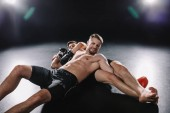 strong shirtless mma fighter doing painful joint lock to another sportsman on floor