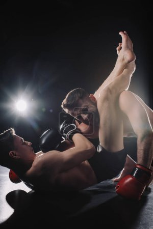 Photo pour Strong shirtless mma fighter doing painful joint lock with legs to another sportsman on floor - image libre de droit