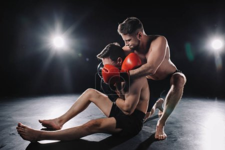 Photo for Strong mma fighter in boxing gloves doing chokehold to another sportsman on floor - Royalty Free Image