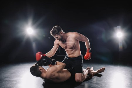 Photo pour Strong mma fighter in boxing gloves punching opponent while sportsman lying on floor - image libre de droit
