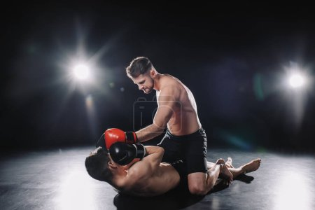 Photo pour Strong mma fighter in boxing gloves sitting on opponent and punching him in head while sportsman lying on floor - image libre de droit