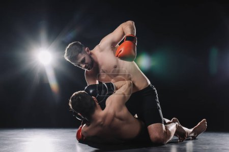 Photo for Shirtless strong mma fighter in boxing gloves punching opponent in head while sportsman lying on floor - Royalty Free Image