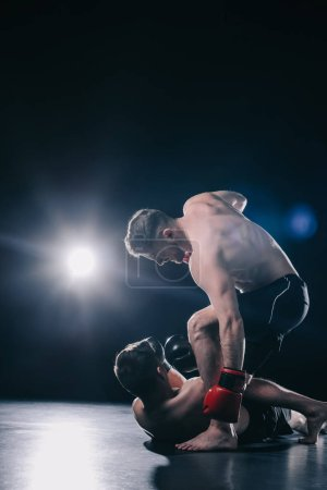 Photo pour Shirtless strong mma fighter in boxing gloves standing above opponent and punching him in head while sportsman lying on floor - image libre de droit