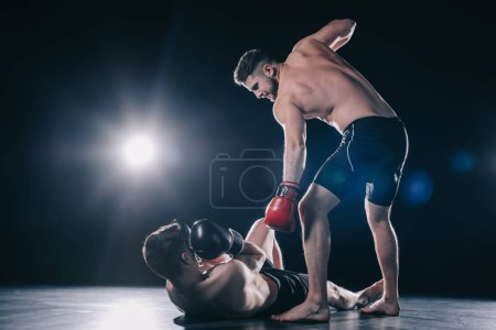 Photo pour Shirtless strong mma fighter in boxing gloves standing above opponent while sportsman lying on floor - image libre de droit