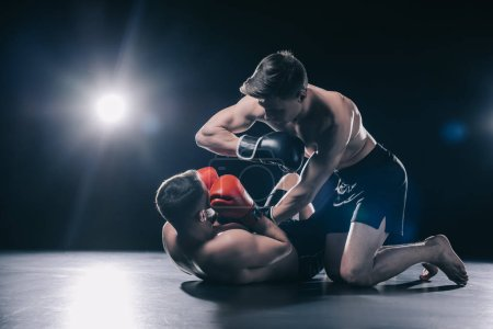 Photo pour Shirtless strong mma fighter in boxing gloves standing on knees above opponent and punching him with elbow - image libre de droit