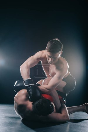 Photo for Shirtless strong mma fighter in boxing gloves clinching opponent on floor - Royalty Free Image