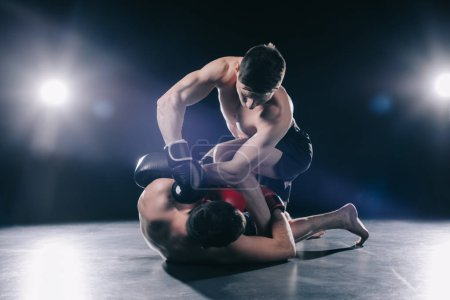 shirtless muscular strong mma fighter in boxing gloves clinching opponent on floor