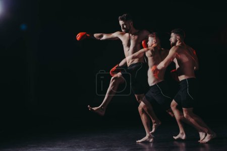 Photo for Multiple exposure of strong shirtless muscular mma fighter in boxing gloves doing punch in jump - Royalty Free Image