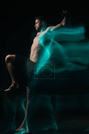 Photo for Long exposure of sporty muscular mma fighter jumping in green light on black - Royalty Free Image