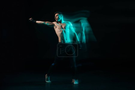 Photo for Long exposure of green light and sporty muscular mma fighter doing punch and looking away - Royalty Free Image