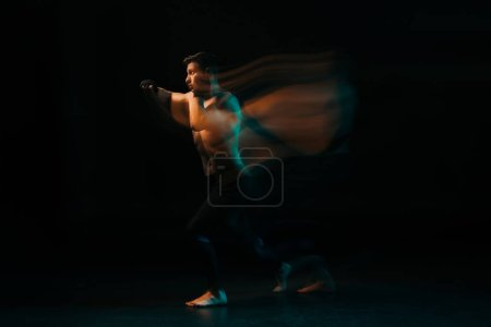Photo for Long exposure of orange and green light and shirtless muscular mma fighter doing punch - Royalty Free Image