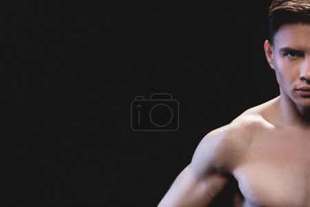 Photo for Partial view of handsome muscular sportsman looking at camera isolated on black - Royalty Free Image